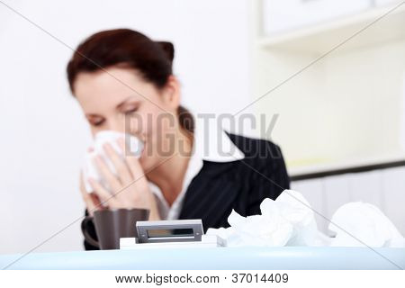 Portrait of a sick young business woman blowing her nose. Focused on tissues on the desk