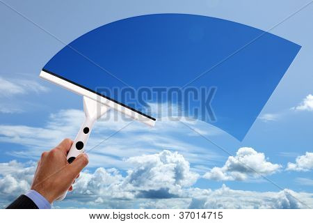 Window cleaner using a squeegee to clear the blue sky above