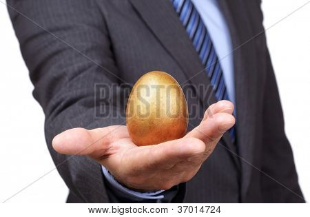Businessman holding a golden egg concept for wealth, investment and retirement