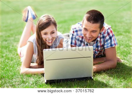 Young couple lying on grass with laptop