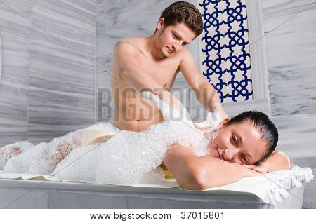 Male bath attendant massages and bathes young female customer of a Turkish bath