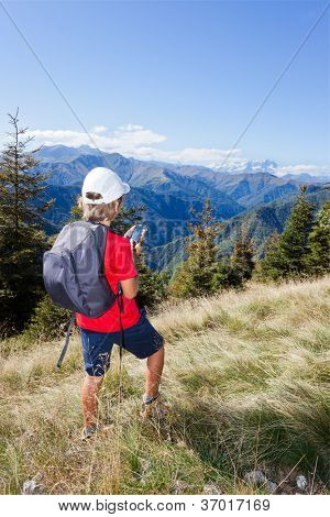 Young boy standing along a mountain path using a  smartphone for checking his gps position. Summer season, clear blue sky. Boy is wearing a red shirt, white cap and a grey backpack. west italian Alps.