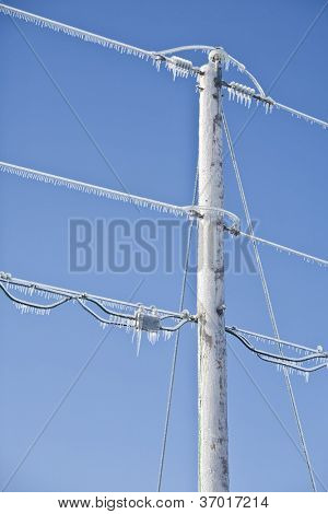 Power pole and lines covered in ice and icicles.