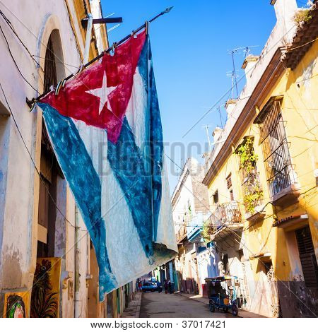 Street  sidelined by decaying buildings in Old Havana with a big cuban flag (square format)