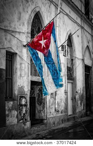 Colorful cuban flag in a shabby black and white street in Havana