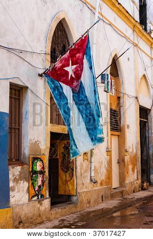 Shabby decaying house in Old Havana with a big cuban flag