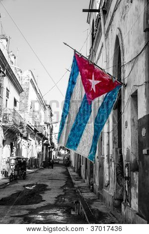 Black and white street scene in Old Havana with a colorful cuban flag