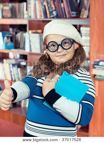 Girl in thick-lensed glasses showing thumb up