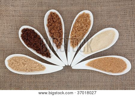 Selection of demarara, granulated, molasses, muscovado, crystal and light brown sugar in white bowls over hessian background.