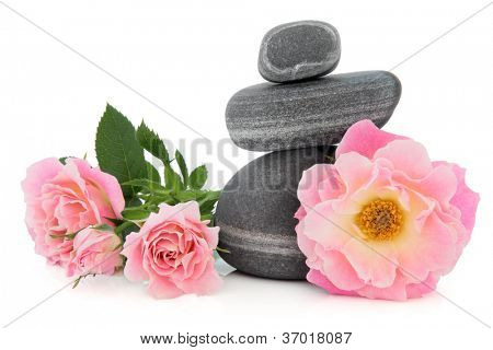 Pink rose flower arrangement with spa stones over white background. Carefree days variety.