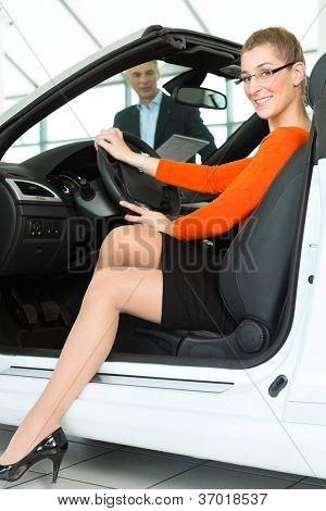 Young woman with mature man sits in car on driver seat with her hand on the steering wheel in a car dealership, obviously she is buying or selling the convertible