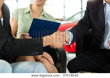 Two men in business suits shaking hands after a successful car purchase in front of a woman holding documents in a light car dealership