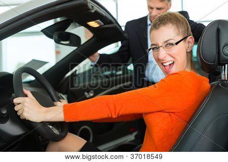 Mujer joven con hombre maduro se sienta en el coche en el asiento del conductor con la mano en el volante en un coche
