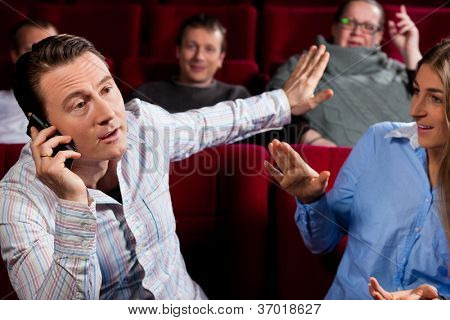 Couple and other people, probably friends, in cinema watching a movie, one is making a phone call and bothering the others