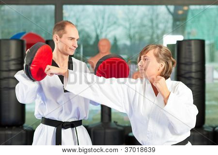 People in a gym in martial arts training exercising Taekwondo, both have a black belt