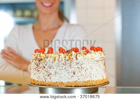 Female baker or pastry chef with torte in bakery