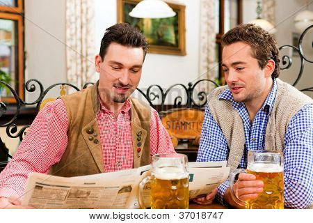 Two friends in Bavarian pub in traditional clothes sitting on their regular table in a pub