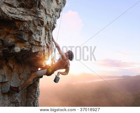 Young man climbing vertical wall with belay with sunrise valley on the background