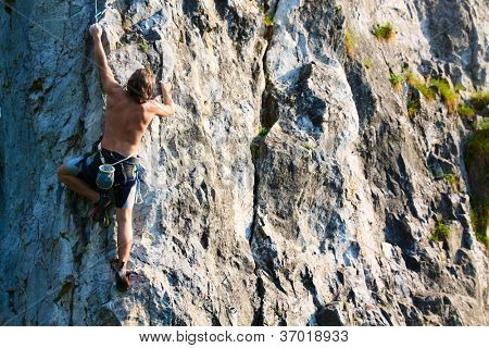 Young man climbing vertical wall with belay