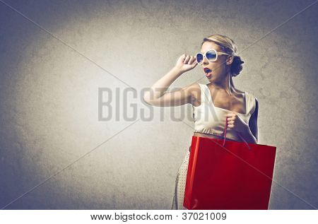 Girl with sunglasses bringing a red bag