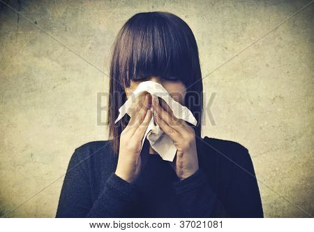 Girl blowing nose with a handkerchief