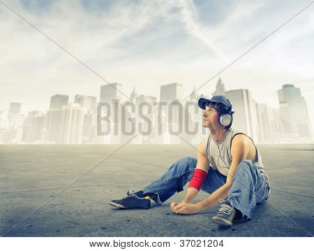 Street boy listening to the music on a ground near New York
