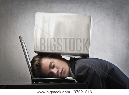 Businessman sleeping on his laptop computer with a pack on his head