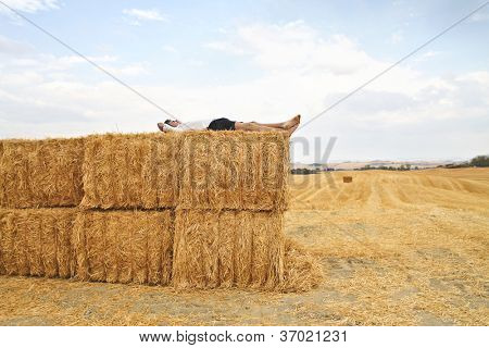 Boy relaxing on some sheaves in the countryside