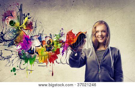 Beautiful blonde girl making a graffiti