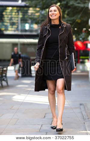 Business woman walking on the street carrying a laptop computer