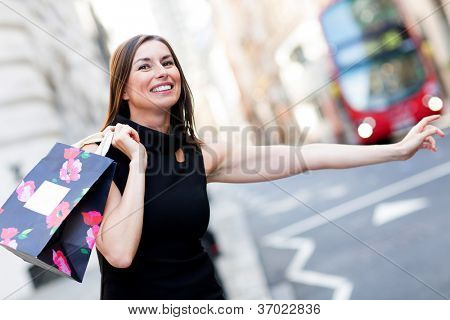 Shopping woman with her arm extended grabbing a taxi