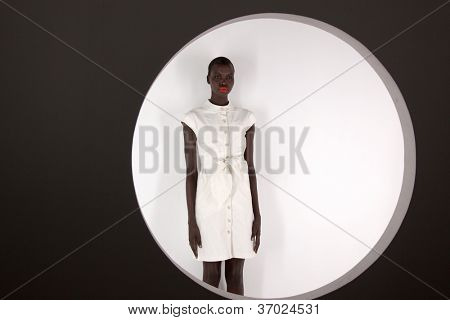 NEW YORK - SEPT 10: A model stands behind a round window portal at the bebeBLACK Spring/Summer 2013 collection presentation during Mercedes-Benz Fashion Week in New York on September 10, 2012.