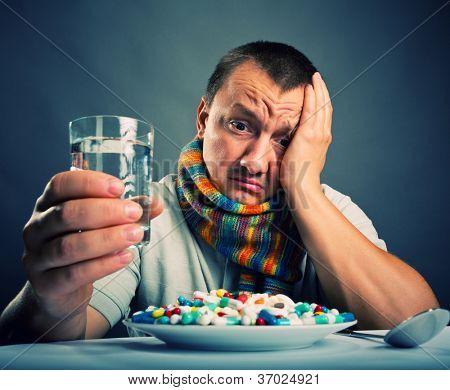 Sad ill man preparing to eat medicines