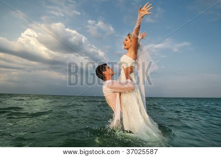 Romantic newly-married couple enjoying a summer vacation. Young groom lifting his bride in sea