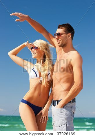 picture of happy couple walking on the beach (focus on woman).