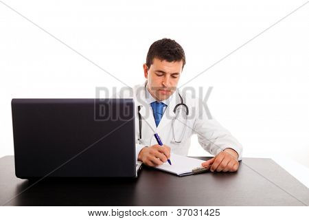 Young doctor writing notes in a notebook at the desk, isolated on white