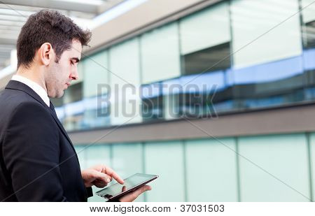 Young businessman using his digital tablet at the office