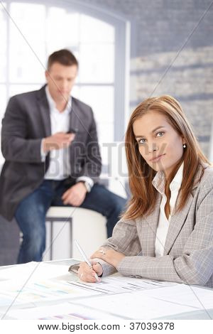 Attractive woman working at desk in bright office, smiling, man texting in background.