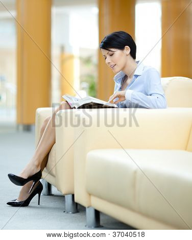 Woman rests at the sofa reading book at the hall