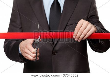 A man cutting a scarlet satin ribbon with scissors, isolated on white