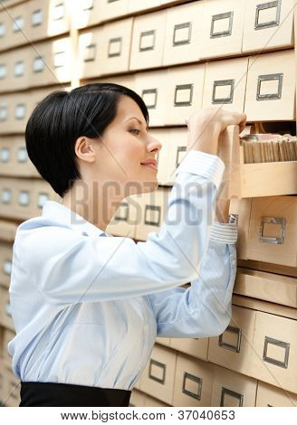 Woman looks for something in card catalog composed of set of wood boxes at the library. Education and research