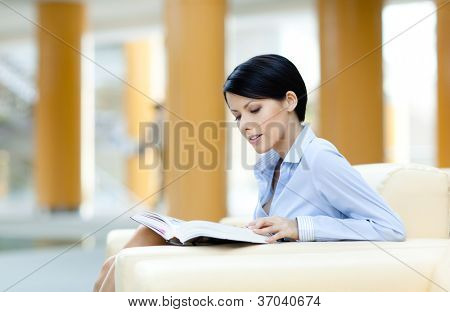 Business woman rests at the white leather sofa reading book at the hall
