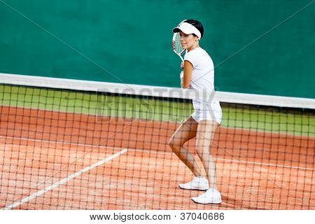 Sportswoman at the tennis court with racquet. Match