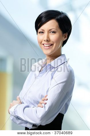 Portrait of a handsome successful business woman wearing white shirt and black skirt at business centre