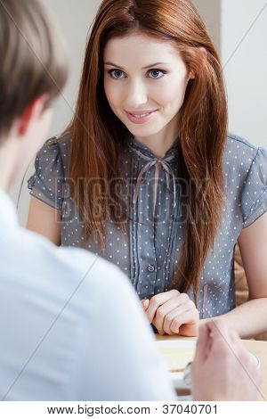 Woman talks with man sitting at the table at the cafeteria