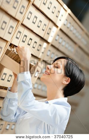 Woman seeks something in card catalog composed of set of wood boxes at the library. Studying