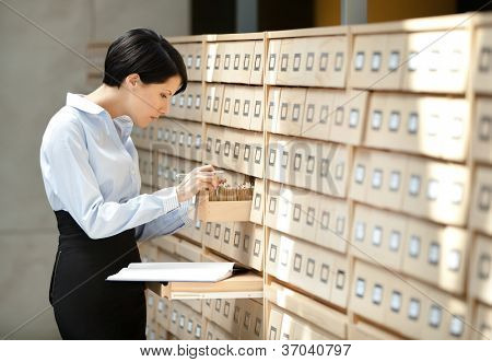 Woman seeks something in card catalog composed of set of wood boxes at the library. Knowledge