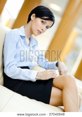 Business woman rests at the sofa handing book at the hall