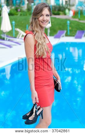 smiley beautiful woman in red dress standing near open-air swimming pool and holding her shoes