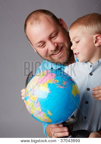 father in thirties and toddler boy of three years old learning geography with an earth globe